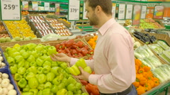 Handsome man picking up green bell peppers Stock Footage