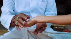Balinese priest taking women's hand to do palm reading Stock Footage