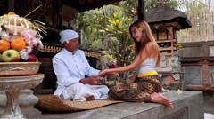 Balinese priest holding women's hand doing palm reading in a small temple Stock Footage