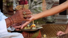 Balinese priest holding women's hand doing palm reading Stock Footage