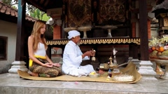 Balinese priest praying ceremony with a young caucasian woman in a small temple Stock Footage