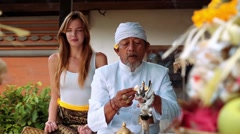 Balinese priest praying ceremony with a young caucasian woman in a small temple - stock footage