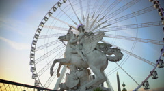 Ferris wheel rotating behind marble statue of equestrian riding winged stallion - stock footage