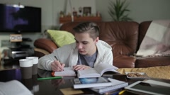 A handsome student writting notes in the notebook. Stock Footage