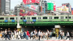 Tokyo - People on crosswalk with colourful billboards and train  passing by. 4K - stock footage