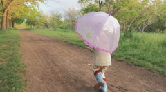 Little girl with umbrella running and laughing in park on the path, slow motion - stock footage