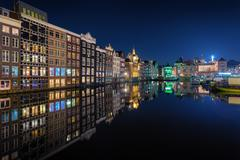 Beautiful traditional old buildings on canal in Amsterdam at night Stock Photos