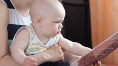 Cute little child play with book while sitting with mom - stock footage