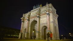Many people walking by triumphal arch in Place du Carrousel, night Paris, France - stock footage