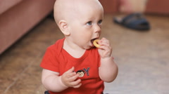 Cute baby boy eating child biscuit Stock Footage
