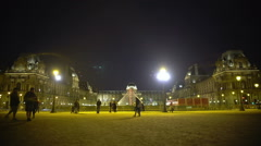 Dark sky over brightly illuminated Louvre Museum palace and pyramid, night Paris - stock footage
