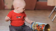 Adorable little boy playing with round box, smiling. Stock Footage