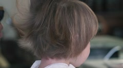 Hairdresser cuts the little girl hair with clipper in barbershop. Close up Stock Footage