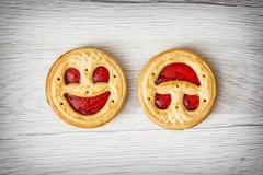 Two round biscuits smiling faces, humorous sweet food - stock photo