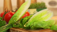 Chicory salad falls on wooden table in slowmotion Stock Footage