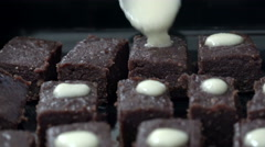 Pouring chocolate on cube brownies cakes, home preparation Stock Footage