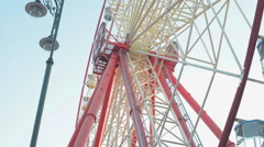 Giant ferris wheel against blue sky and white cloud which mean an amusement-park Stock Footage