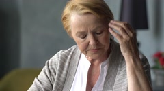 Elderly woman with headache takes a pill Stock Footage
