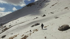 A man walking alone with a wolf on the snow-capped mountains. Aerial video. N. Stock Footage
