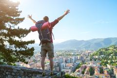 young traveler standing with open arms on the city landscape - stock photo