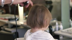 Hairdresser doing hair the little girl with a hair dryer. Close up Stock Footage