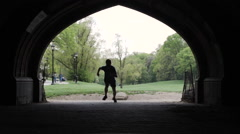Silhouette of a man running running through a park in slow motion - stock footage