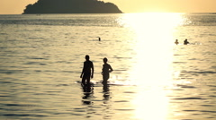 Silhouette of couple walking on the sea during sunset, slow motion shot at 120fp - stock footage