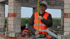 Builder using measuring tape in the unfinished building - stock footage