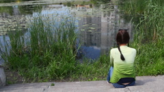 Beautiful sad young woman sitting alone near lake in park, copy space Stock Footage