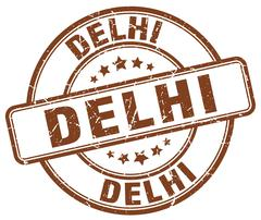 Delhi brown grunge round vintage rubber stamp - stock illustration