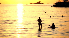 Happy people sitting in the sea during sunset, super slow motion - stock footage