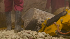 Are Working, Stones, Ground, Rubber Boots. Excavator Bucket Lying on the Stock Footage