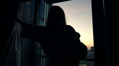 Silhouette of woman unveil curtains and admire sunset form the window, super slo Stock Footage