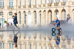 People having fun in a mirror fountain in Bordeaux, France Stock Photos