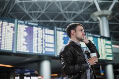Smiling young traveller man at the airport talking on phone in front of - stock photo