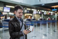 Portrait of young handsome man walking in modern airport terminal, texting - stock photo