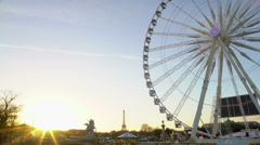 Sunset in Paris, Eiffel Tower on cityscape horizon, observation wheel rotating Stock Footage