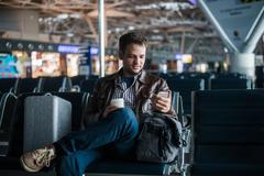 Handsome smiling man in casual wear holding luggage and messaging through his - stock photo
