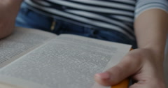 Close-up of female hand turning book page in library Stock Footage