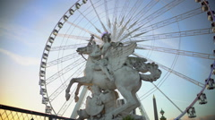 Ferris wheel rotating behind marble statue of equestrian riding winged stallion Stock Footage