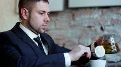 Businessman drinks tea at the cafe Stock Footage