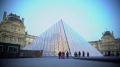 Groups of tourists walking by glass pyramid near Louvre Palace in Paris, France Stock Footage