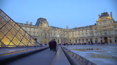 Fascinated people viewing majestic glass pyramids at famous Louvre Museum, Paris Stock Footage