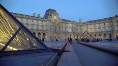 Many people walking in Louvre Palace yard, viewing glass pyramid constructions Stock Footage