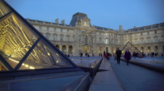 Crowds of travelers enjoying visit to Louvre Museum, viewing glass pyramids Stock Footage
