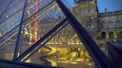 Tourists visiting Louvre art museum, view through glass pyramid, tour to Paris Stock Footage