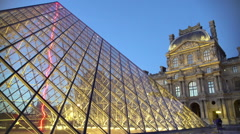 Night view of illuminated Louvre Palace with glass pyramid, famous Paris sights Stock Footage