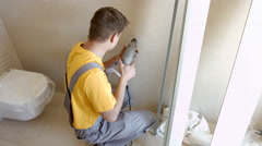Young Man is Drilling Hole in the Wall With a Drill. Mounting Works Stock Footage