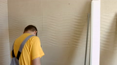 Young Worker Attaches Strip to the Wall With the Help of Power Screwdrivers. - stock footage