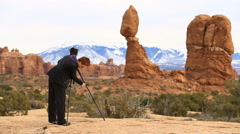 Woman setting up camera on tripod in desert landscape - stock footage